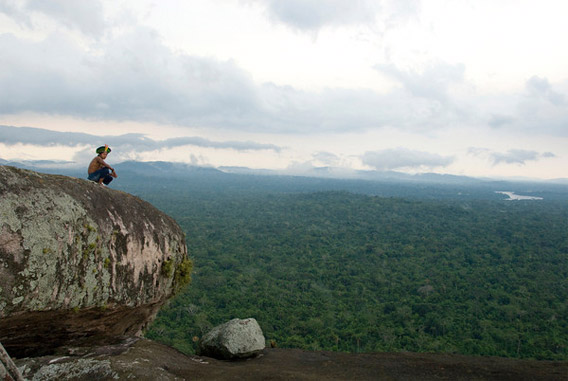 Kayapo man on top of the mountains with a landscape view of the Amazon forest