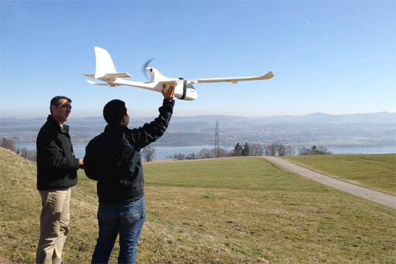 Koh and Wich testing their drone in Switzerland. The conservation drone has been equipped with various cameras including the GoPro HD Hero, the Canon IXUS 220 HS, and the Pentax Optio WG-1 GPS. Image courtesy of Lian Pin Koh.