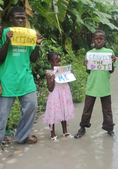 Haiti's youth stand in flooded streets to connect the dots between climate change and severe floods. Photo courtesy of 350.org.
