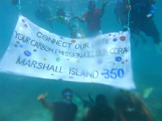 Activists hold a banner in front of a damaged coral reef in the vulnerable Marshall islands. Rising temperatures and increased CO2 uptake are raising the acidity of the ocean, which bleaches and ultimately may kill fragile coral reefs. Photo courtesy of: 350.org.