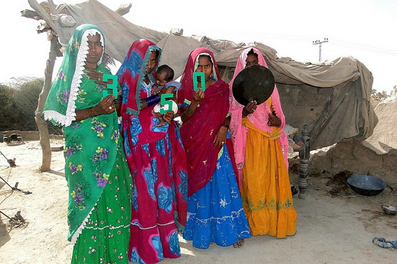 Women hold a dot outside of the temporary structure that they have been living in since the devastating 2010 floods destroyed their home. Photo courtesy of: 350.org.
