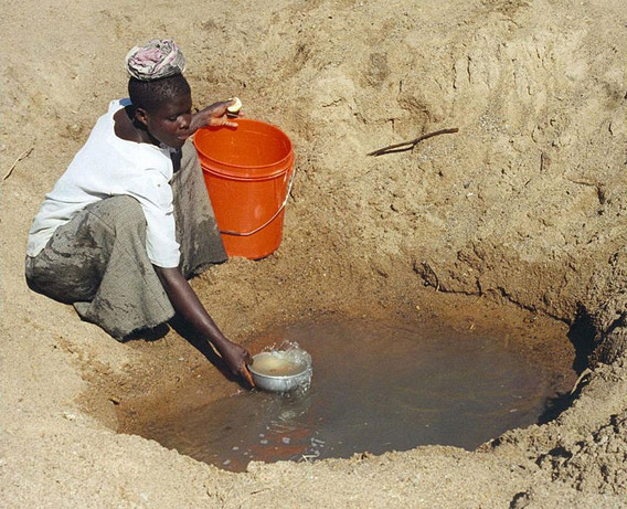 Access to clean water is most difficult in Africa. Here a woman in Tanzania gathers water from a hole in a riverbed. Photo by: Bob Metcalf.