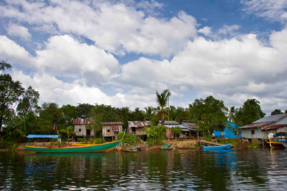 Houses along the river on the outskirts of Chi Phat. Photo courtesy of Suwanna Gauntlett.