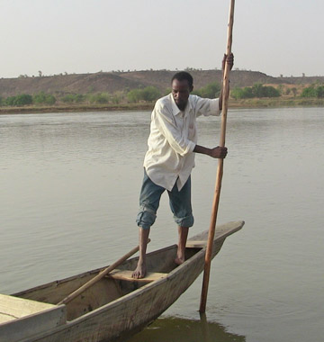 A fisherman embarks on a sunset trip down the Niger River valley on board his only source of income, a pirogue, a wooden canoe made of hollowed tree trunks, usually used for transport, fishing and hunting activities. Photo by: Linda Leila Diatta.