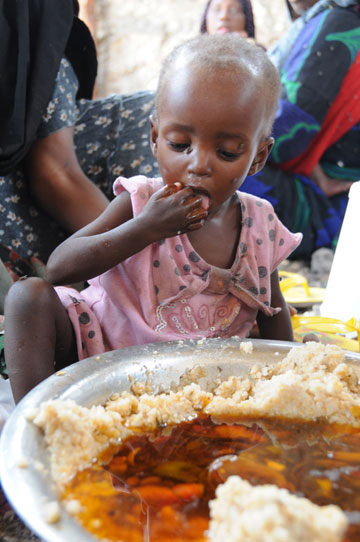 A hungry child eats in Somalia. Lack of government and militant groups have helped create famine conditions in Southern Somalia. Thousands of Somali refugees have escaped to Kenya and Ethiopia, straining refugee camps and supplies. Photo by: Photo by: © David Orr/WFP.