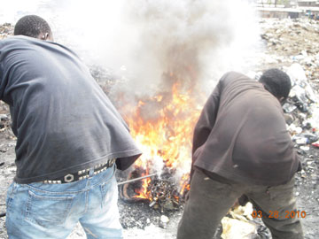 Boys stoke the fire containing the wires.