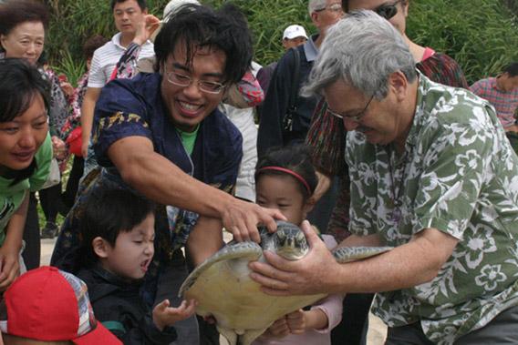 放生前Frederick Yeh(左)、George Balazs(右)和孩子们一起观赏海龟Crush。照片来自911国际海龟保护组织