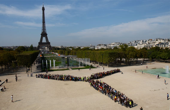 People create the image of a turbine backed by the Eifel Tower in Paris. Photo by: Nicolas Chauveau.