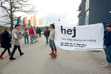 Protestors with a sign in Swedish that reads: Hello, our furniture is made of old-growth forests. At IKEA you get low prices at any cost.