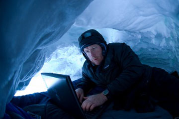 Hugh Powell blogging in a snow cave in Antarctica. Photo by: Chris Linder.